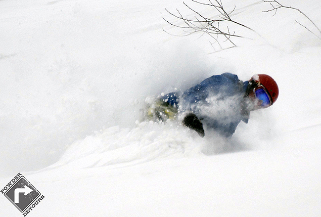 Bob laying over a toe-side in the pow - Powder Detours